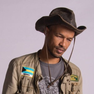 bust photo of Ancilleno Davis in field hat with cargo jacket with Bahamas flag patch on right breast