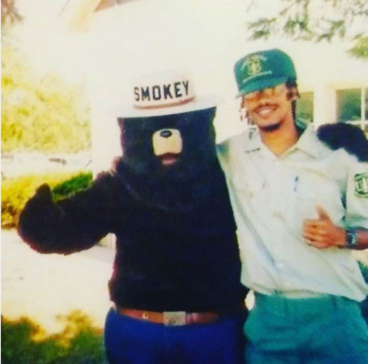 Ancilleno Davis (right) in USFS uniform stands hugging Smokey the Bear. They both have one arm around the other's shoulder and are giving a thumbs up with the other hand.